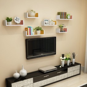 Небольшие полочки над телевизором в гостиной