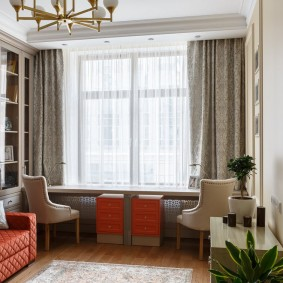 Длинный стол перед окном небольшой комнаты