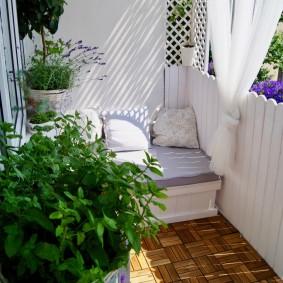 Удобный диванчик на балконе с растениями