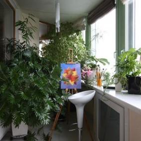 Барный стул на балконе с зелеными растениями