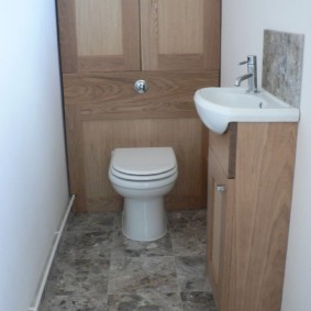 Узкая раковина на тумбе в туалете