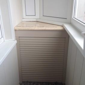 Маленький шкафчик в углу застекленного балкона