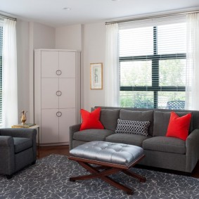 Красные подушки на сером диване