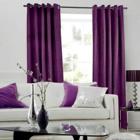 Фиолетовые портьеры в зале с белым диваном