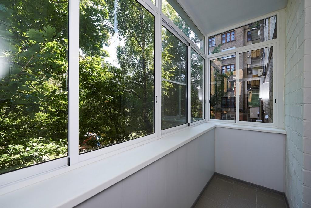 Пластиковый подоконник под раздвижными окнами на балконе
