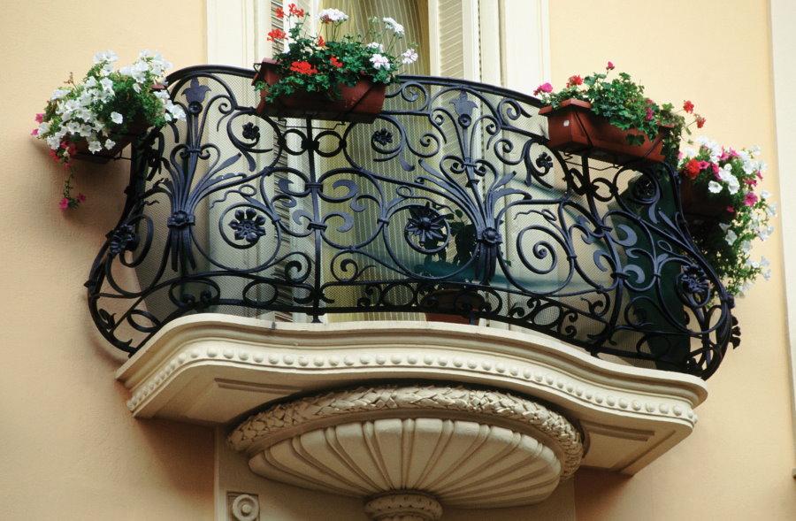 Узкий кованный балкон с цветами в контейнерах