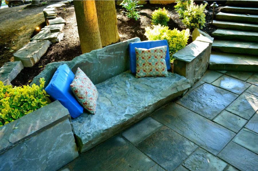 Мягкие подушки на каменной скамейке в саду