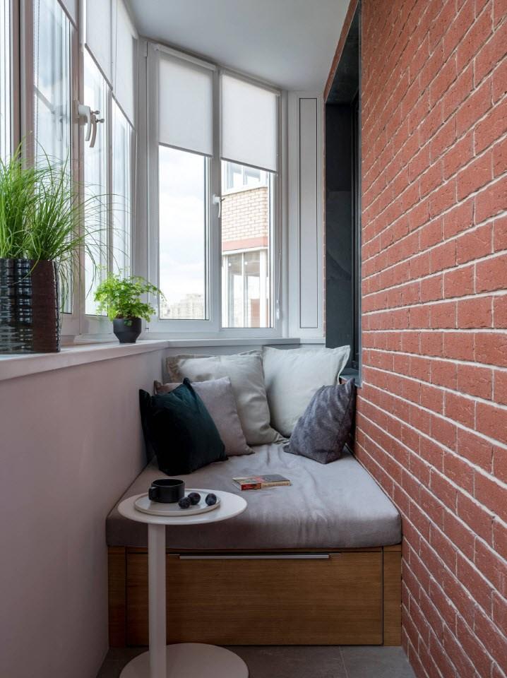 Небольшой диванчик на балконе с кирпичной отделкой