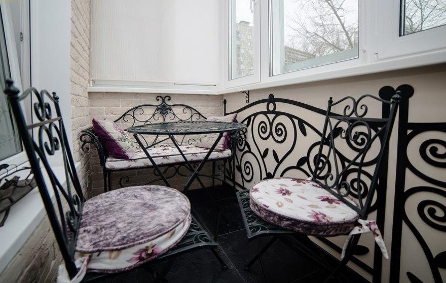 Кованные стульчики на балконе с пластиковыми окнами