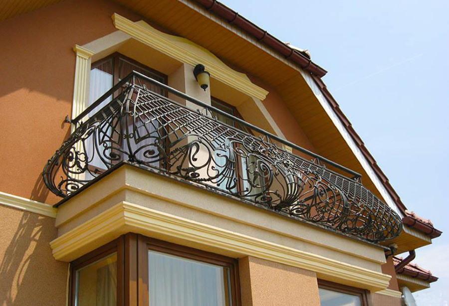 Кованный балкон на фасаде загородного дома