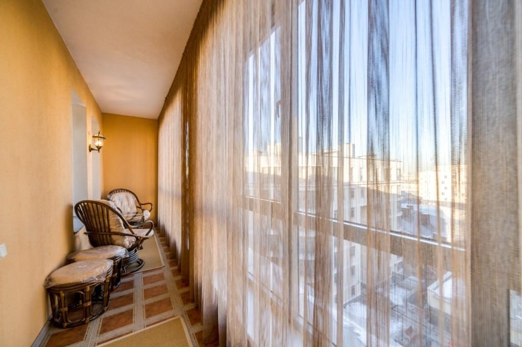 Легкие шторы на панорамных окнах балкона