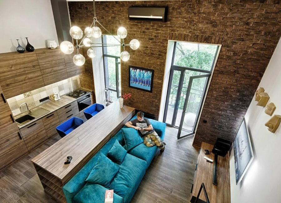 Бирюзовый диван в квартире-студии стиля лофт