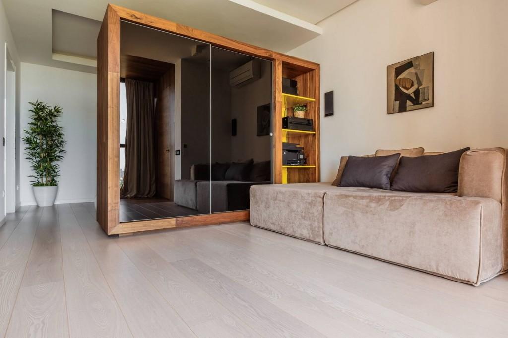 Массивный шкаф в роли разделителя пространства гостиной