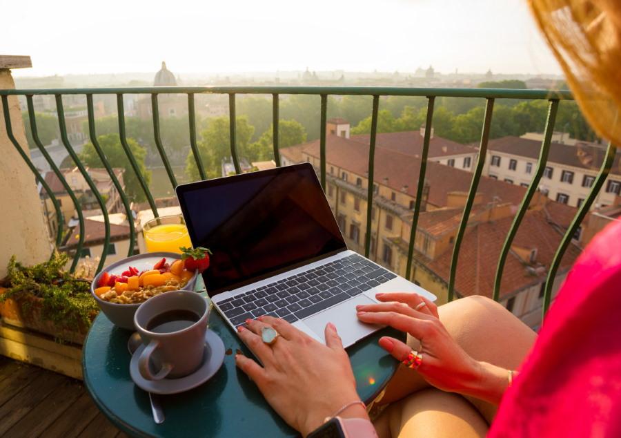 Девушка с ноутбуком на открытом балконе
