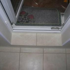 Порог из светлой плитки перед балконной дверью