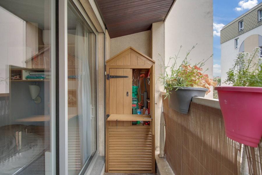 Деревянный шкаф в форме домика на открытой лоджии