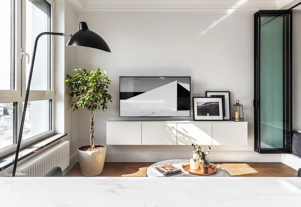 Навесная тумба под телевизором в маленькой гостиной