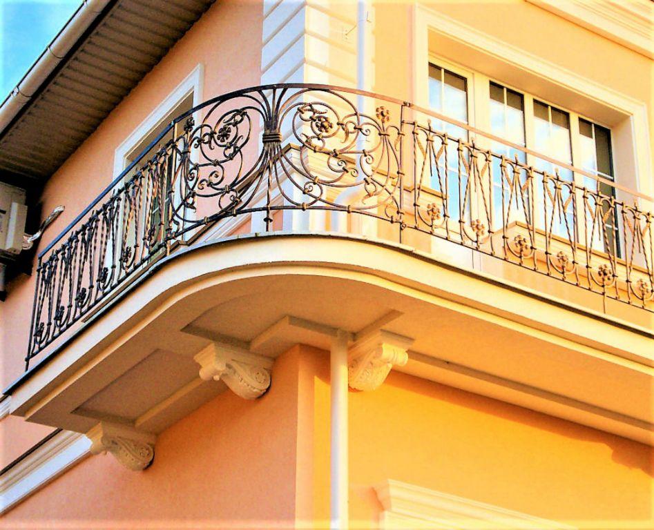 Красивый кованный балкон на углу частного дома