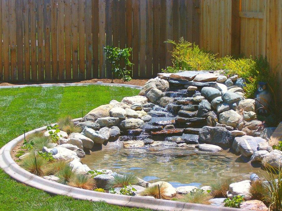 Водопад из камня на участке с деревянным забором