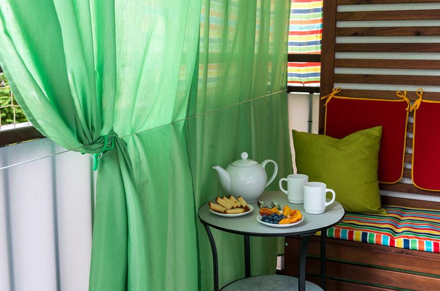 Зеленая шторка на балконе городской квартиры