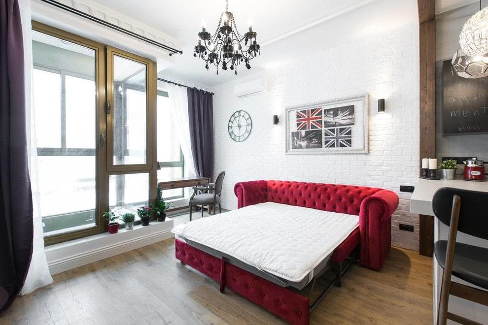 Бардовый раскладной диван в гостиной с большими окнами