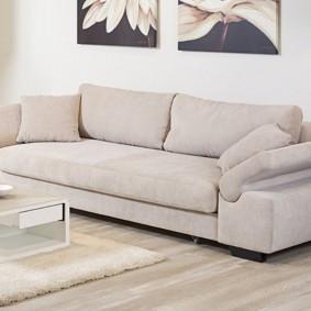 Большой раскладной диван у стены в гостиной