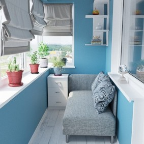 Небольшой диванчик на балконе с голубыми стенами