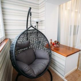 Серое кресло на утепленном балконе