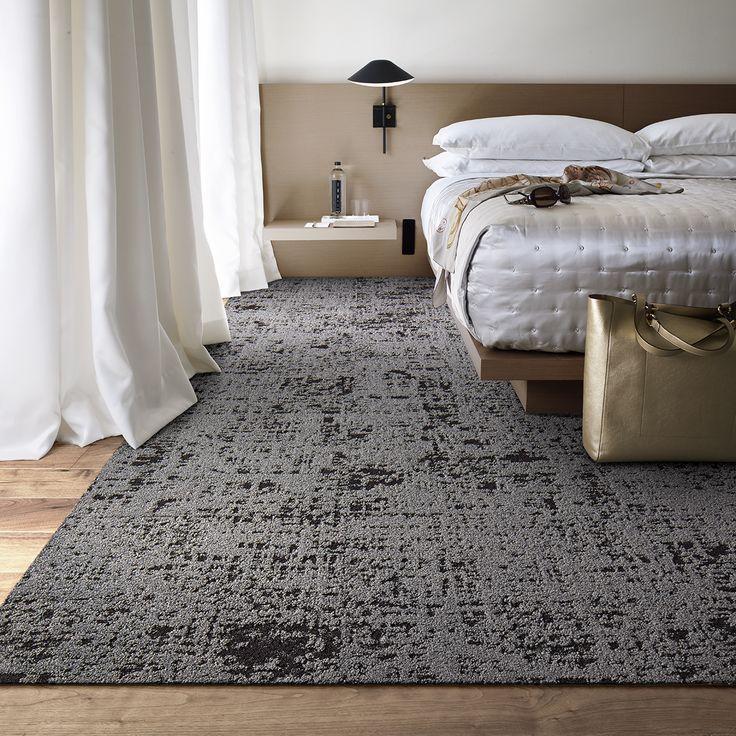 Серый ковер перед кроватью в спальне