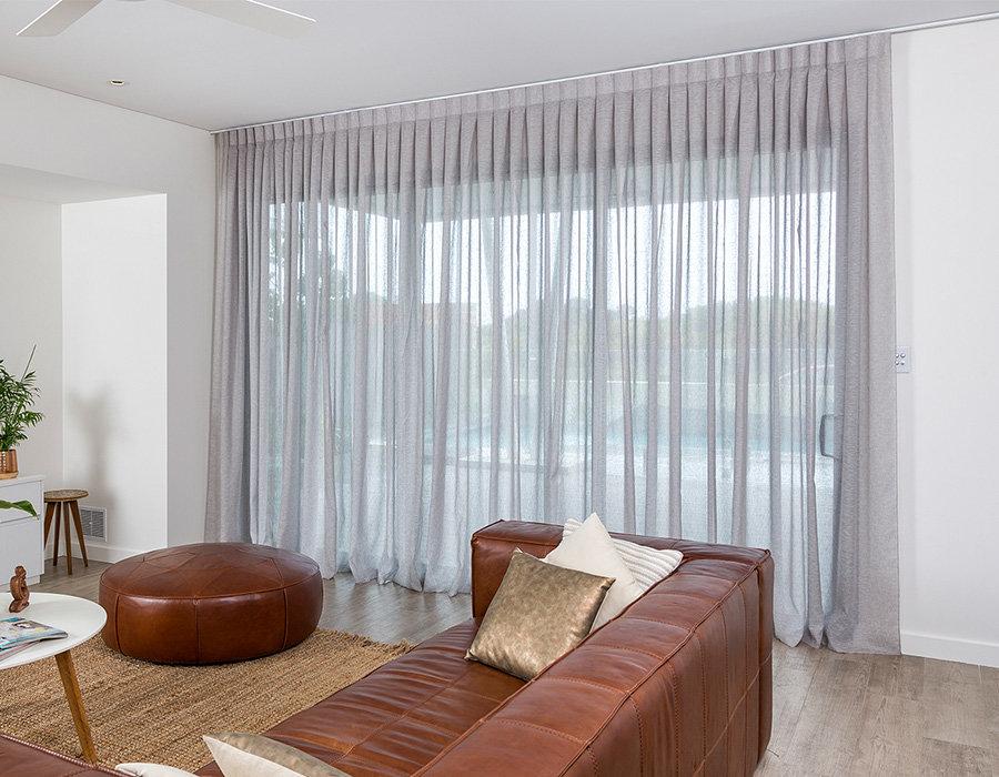 Светло-серый тюль в гостиной с коричневым диваном
