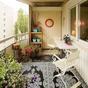 Комфортное место для отдыха на балконе с цветами