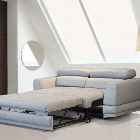 Раскладной диван под окном в мансарде