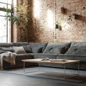 Серый угловой диван у кирпичной стены
