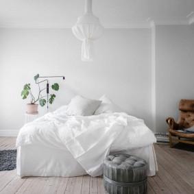 Серый пуф около белой кровати