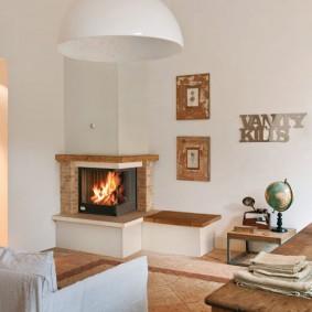 Светлая гостиная с камином в углу комнаты