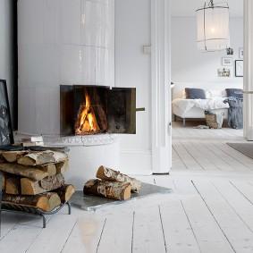 Белый камин в углу гостиной скандинавского стиля