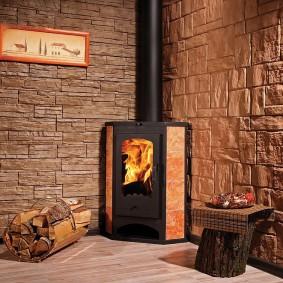 Металлический камин в комнате с каменным декором