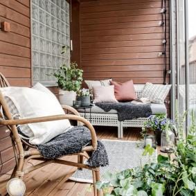 Плетенная мебель на балконе кирпичной многоэтажки