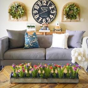 живые цветы в контейнере перед диваном