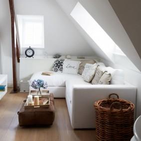 Белый диван под окном в мансарде