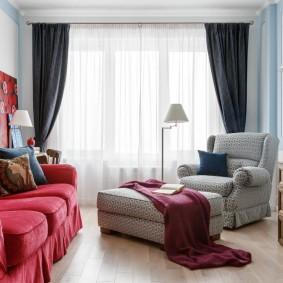 Красный диван в зале с черными шторами