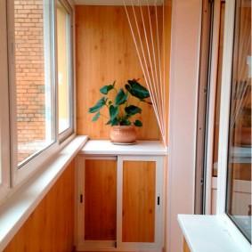 Живой цветок на балконной тумбочке