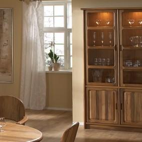 Деревянный шкаф с посудой возле окна в зале