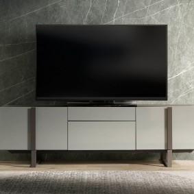 Широкоформатный телевизор на тумбе с гладкими фасадами