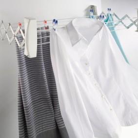 Белая рубашка на настенной сушилке