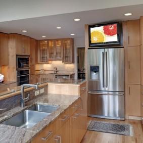 Компактный телевизор над холодильником на кухне