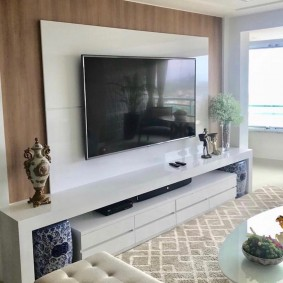 Черный телевизор на белых пластиковых панелях