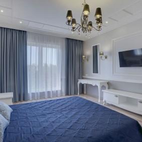 Синее покрывало в спальне с белой мебелью