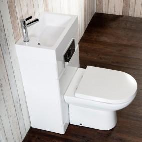 Белая сантехника на коричневом полу в ванной