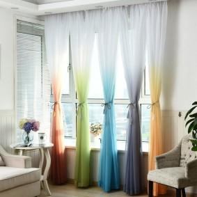 Разноцветный тюль на небольшом окне в зале